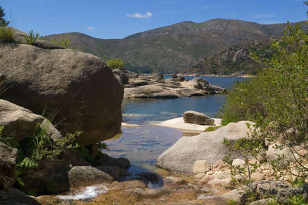 A small creek flowing amongst rocks into the lake. National Park of Peneda-Ger�s, Portugal Stock Photo