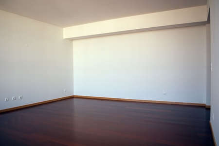Completely empty plain living room, of white walls and reddish brown wooden floor. Soft light.