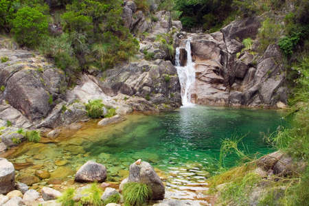 A small waterfall and green lagoon hidden in the mountains. Arado river, Peneda-Gerês National Park, Portugal. Stock Photo
