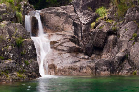 Waterfall closeup over green water. Arado river, Ger�s National Park, Portugal.