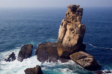 Huge rocks and cliffs extending to the blue ocean and populated with sea birds. Nau dos Corvos, Peniche, Portugal Stock Photo - 5736841