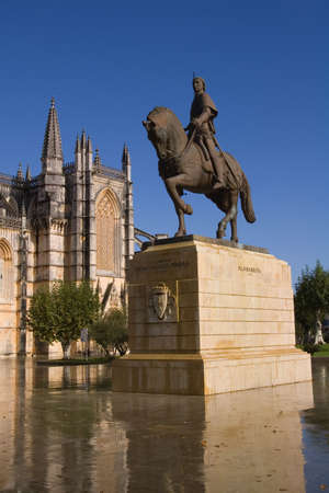 Statue of Knight Nuno Álvares Pereira. Batalha Monastery in the background. Portugal.