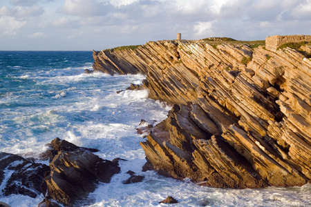 Sharp sedimentary rocks by the sea lit by the sun at the end of the day. Baleal, Peniche, Portugal