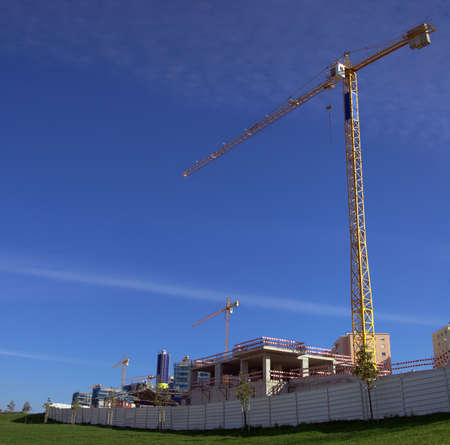 Construction site with yellow cranes over blue sky and green grass Stock Photo