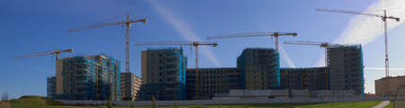Construction site with yellow cranes over blue sky behind green grass Stock Photo
