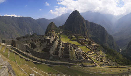Machu Picchu, main gate, surrounding wall and exterior stairway under uneven sunlight