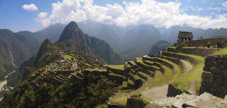 gradas: Panoramana de Machu Picchu, la Guardia casa, terrazas de la agricultura, Wayna Picchu y monta�as que la rodean en segundo plano.  Foto de archivo