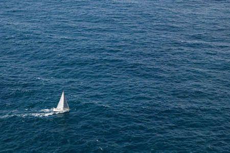 A white sail boat over blue ocean water.