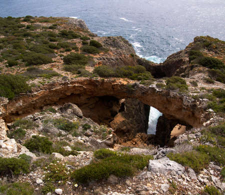 seismic: An old seismic fail reaching the ocean with two natural stone bridges. Focus on the first bridge. Cape Espichel, Sesimbra, Portugal.