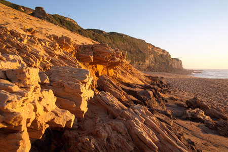 Sandstone breaking down at the beach under sunset light. Meco, Sesimbra, Portugal.