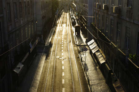 Paulo street in Lisbon by sunset with electric vehicle rails reflecting the sunlight Stock Photo