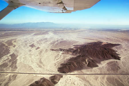 Nazca desert and panamerican highway seen from above, under the wing of a Nasca Lines airplane. Peru. Focus on the ground.