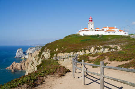 roca: Cape Roca lighthouse facing the ocean beyond a wood fence. Focus on foreground and lighthouse.