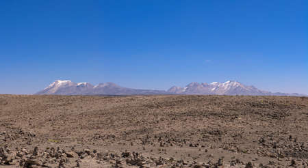 aguada: Highland peruvian desertic plains in Reserva Natural de Salinas e Aguada Blanca. 5000 meters above sea level and snowed peaks. Stone heaps are all over the ground as offerings to the gods. Pata Pampa, Arequipa, Peru. Stock Photo