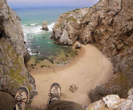 inaccessible: Feet hanging from a cliff over a small, inaccessible, deserted beach. Sintra, Portugal.