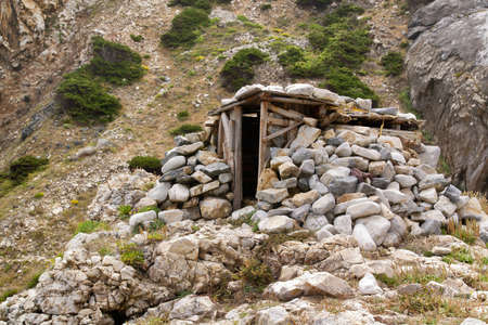 A shelter made of stone and wood built on the mountain slope. Focus on shelter. Stock Photo - 11353389