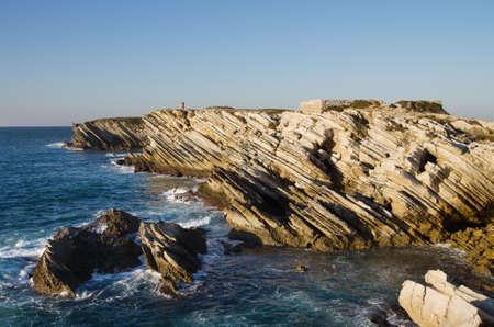 Sharp sedimentary rocks of Baleal island facing the ocean and crushing waves. Peniche, Portugal.
