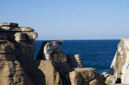 carbonate: Conical carbonate rocks formation against the blue ocean. Cape Carvoeiro, Peniche, Portugal.