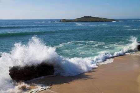 Wave breaking into a rock in Pessegueiro Beach. Pessegueiro Island in the near horizon. Porto Covo, Portugal.