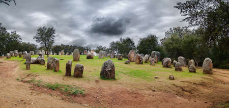 Almendres Cromlech overview seen from below under a dark clouded sky. Evora, Portugal. Stock Photo - 16391435