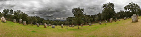 Panorama of Almendres Cromlech lower part menhirs under a dark dramatic clouded sky. Evora, Portugal. photo
