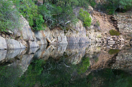 mirror on the water: Mirror water reflection of rocks in the river bank.