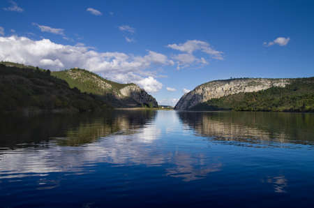 Clouded blue sky reflected in the calm Tagus river lake