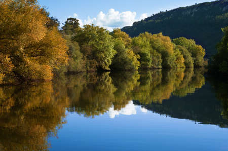 Autumn composition of green and brown riverbank trees and blue sky reflecting on river calm water.