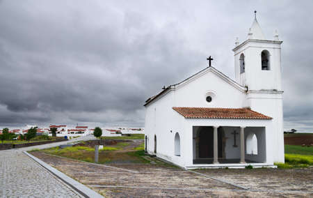 White chapel of Aldeia da Luz under an overcast sky. Alentejo, Portugal.