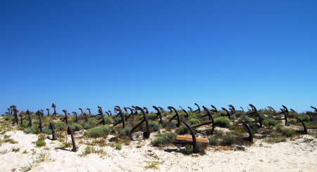 Wide landscape view of an anchor cemetery on the dunes of Barril beach against a deep blue sky  Tavira, Algarve, Portugal  Stock Photo