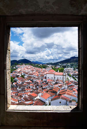 Overview of the historic part of town of Castelo de Vide framed through an old stone window  Alentejo, Portugal  Stock Photo
