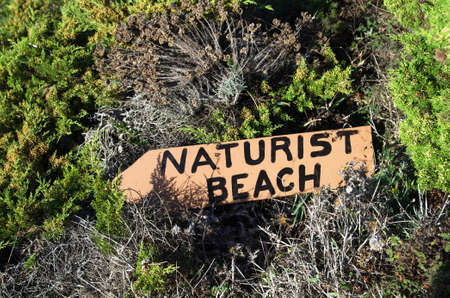 nudism: Naturist beach sign lost in the middle of the vegetation.