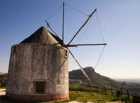 Old and abandoned traditional windmill with Palmela in the foreground. Portugal. Stock Photo