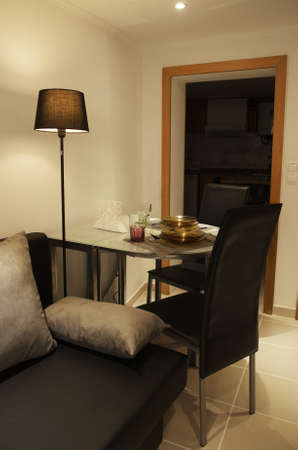 dinning table: A small and cozy space with dinning table, partially unfolded to serve two people, glass dishes and cups, black leather chairs and stand lamp.