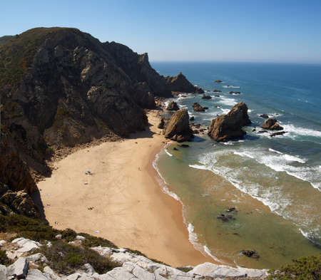 naturist: Ursa Beach and its rocks facing the ocean seen from the top of the cliff. A remote naturist beach near Cape Roca, Sintra, Portugal. Blue ocean and sky.