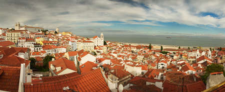 panoramics: Overview of Alfama, the most famous typical neighbourhood of Lisbon. Cityscape as seen from Portas do Sol viewpoint, facing tagus river, sunlit and under clouded sky. Portugal.