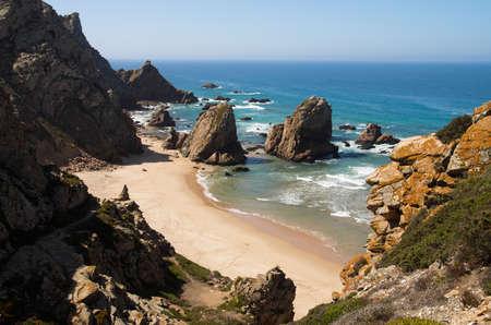 naturist: High perspective of Ursa Beach and its rocks facing the ocean. A remote naturist beach near Cape Roca, Sintra, Portugal. Blue ocean and sky.