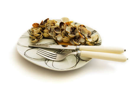 An end of meal dish of empty shells of cockle and clam, knife and fork set apart.