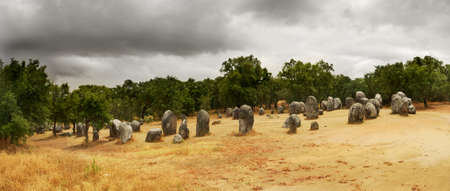 megalith: Almendres Cromlech megalithic monument, with its almond shaped menhirs, lit by the sun but under a dark clouded sky. Evora, Portugal. Stock Photo