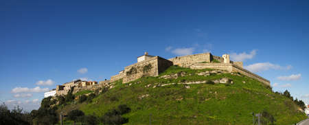 from below: Panorama of Palmela castle seen from south below. Deep green grass slopes under a deep blue sky. Setubal, Portugal.