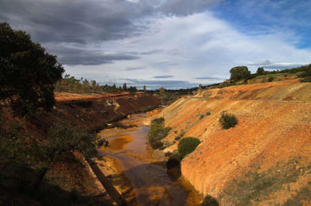 scoria: Yellow and red sulfur and iron polluted river scoria valley at Sao Domingos abandoned mine. Mertola, Alentejo, Portugal. Stock Photo