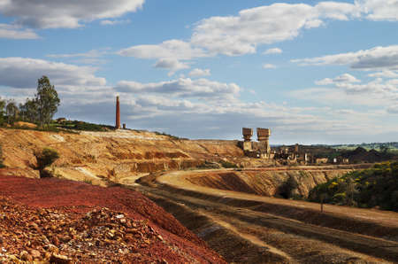 scoria: Abandoned railway path bend between gravel and red scoria. Sulfur extraction oven at the background and bright blue clouded sky. Sao Domingos Mine, Alentejo, Portugal.