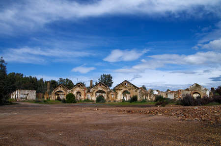 The remains of railway workshop buildings at abandoned mines of Sao Domingos against a blue clouded sky. Mertola, Alentejo, Portugal.
