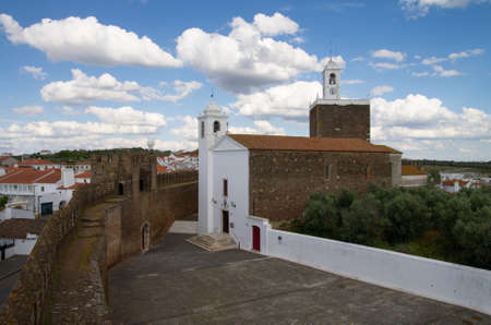 High view of Alandroal church along castle defensive walls, the surrounding village and clock tower under a bright blue clouded sky. Alentejo, Portugal.