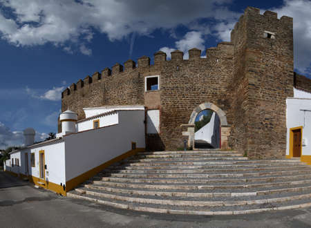 Alandroal castle walls, main gate, stairs and adjacent houses under a bright blue clouded sky. Alentejo, Portugal. Stock Photo