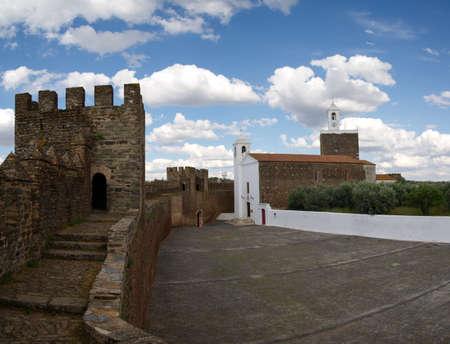 Alandroal castle walls enclosing church facade and clock tower under a bright blue clouded sky. Alentejo, Portugal. Stock Photo