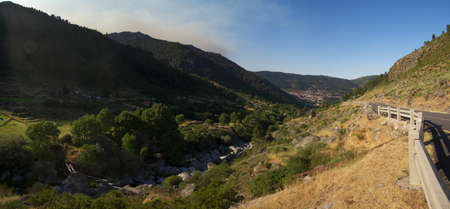 Typical U-shaped glacial valley near Manteigas at Estrela mountain range (Serra da Estrela). Panoramic tarmac road goes along the valley and some clouds are coming trough the mountains. River Zezere runs at the bottom. Portugal.
