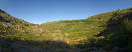 Panorama of green coloured glacial valley at Estrela mountain range (Serra da Estrela) near Manteigas. River Zezere runs at the bottom. Portugal.