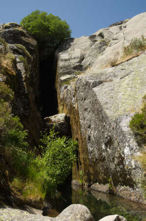 Perpective of a crack in the rocks and a small pond: the birth place of River Zezere at Covao dAmetade. Estrela mountain range (Serra da Estrela), Portugal.