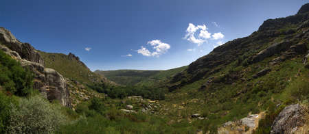 Covao dAmetade, the beginning of Manteigas glacial valley. Trees and vegetation amongst mountains and under a blue sky. Estrela mountain range (Serra da Estrela), Portugal.
